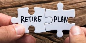 Closeup of hands holding retire plan matching jigsaw pieces against wood